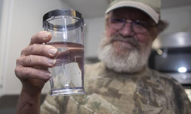"""Flemington Road community member Sam Malpass of Wilmington, N.C. holds a glass of water from his home on Wednesday, Feb. 19, 2014. Malpass and his wife Pat are part of a small community near L.V. Sutton Complex operated by Duke Energy they feel could be polluting well water with spill off and seepage from large coal ash ponds. """"If you want to know what it's like living near a coal ash pond, this is it,"""" said Malpass, 67, a retired carpenter and Vietnam veteran. """"We're afraid to drink the water because we don't know what's in it. We can't eat the fish because we don't know if it's safe anymore. It's changed our lives out here.""""   (AP Photo/Randall Hill)"""