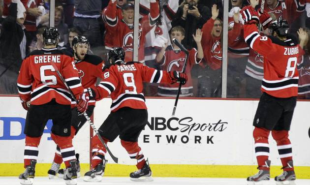 New Jersey Devils' Travis Zajac, center left, celebrates with Andy Greene (6), Zach Parise (9) and Dainius Zubrus (8), of Lithuania, after scoring a goal against the New York Rangers the first period of Game 4 of an NHL hockey Stanley Cup Eastern Conference final playoff series, Monday, May 21, 2012, in Newark, N.J. (AP Photo/Julio Cortez)