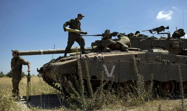 Israeli soldiers load shells in their tank following the first death on the Israeli side of the Golan since the Syrian civil war erupted more than three years ago, near the Israeli village of Alonei Habashan, in the area of Tel Hazeka, close to the Quneitra border crossing in the Israeli-controlled Golan Heights, Sunday, June 22, 2014. A civilian vehicle in the Golan Heights was targeted by forces in neighboring Syria on Sunday in an attack that killed a 15-year-old boy and prompted Israeli tanks to retaliate by firing on Syrian government targets, the Israeli military said. (AP Photo/Oded Balilty)