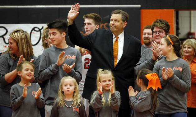 Putnam City coach A.D. Burtschi waves to the crowd as he stands with his family at halftime of the boys high school basketball game between the Pirates and Putnam City West at Putnam City High School in Warr Acres. At halftime, Putnam City named its basketball court after Burtschi, who will retire after this season. (Photo by Nate Billings, The Oklahoman)