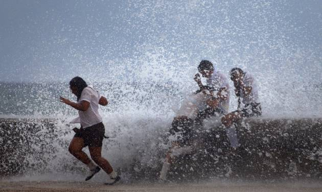 Students play in the waves crashing against the Malecon after the passing of Hurricane Sandy in Havana, Cuba, Thursday, Oct. 25, 2012. Hurricane Sandy blasted across eastern Cuba on Thursday as a potent Category 2 storm and headed for the Bahamas after causing at least two deaths in the Caribbean. (AP Photo/Ramon Espinosa)