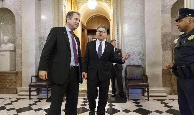 Sen. Sherrod Brown, D-Ohio, left, and Sen. Al Franken, D-Minn., leave the chamber during the vote on restoring jobless benefits for the long-term unemployed, legislation that expired late last year, at the Capitol in Washington, Monday, April 7, 2014. With their 17-day spring break beckoning at the end of the week, House and Senate lawmakers will have to scramble to reach agreement. (AP Photo/J. Scott Applewhite)