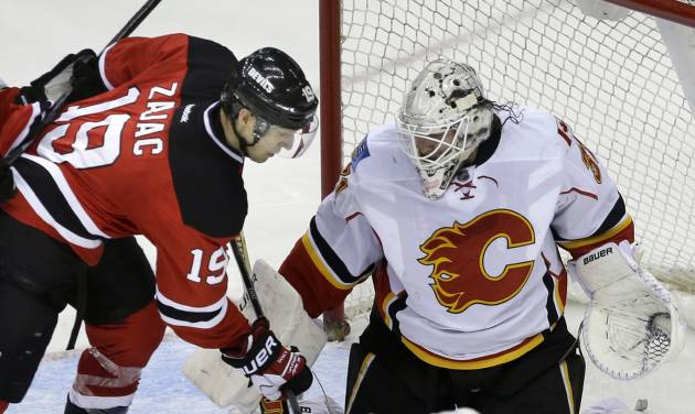 Calgary Flames goalie Karri Ramo, top right, of Finland, blocks a shot by New Jersey Devils' Travis Zajac (19)during the third period of an NHL hockey game in Newark, N.J., Monday, April 7, 2014. The Flames won 1-0. (AP Photo/Mel Evans)