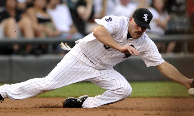 Chicago White Sox third baseman Kevin Youkilis attempts to stop a single hit by Minnesota Twins' Jamey Carrol in the second inning of their baseball game in Chicago, Monday, Sept. 3, 2012. (AP Photo/Paul Beaty