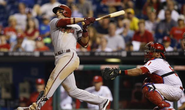 Arizona Diamondbacks' Martin Prado, left, follows through after hitting a go-ahead RBI-sacrifice fly off Philadelphia Phillies relief pitcher Antonio Bastardo during the 10th inning of a baseball game on Saturday, July 26, 2014, in Philadelphia. Phillies catcher Carlos Ruiz, right, looks on. Arizona won 10-6 in 10 innings. (AP Photo/Matt Slocum)
