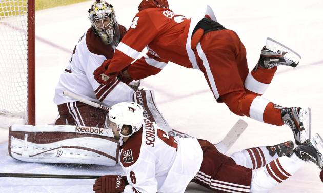 Detroit Red Wings center Damien Brunner, of Switzerland, trips on Phoenix Coyotes defenseman David Schlemko (6) into goalie Mike Smith (41) in the third period of an NHL hockey game in Detroit, Monday, April 22, 2013. Detroit won 4-0. (AP Photo/Paul Sancya)