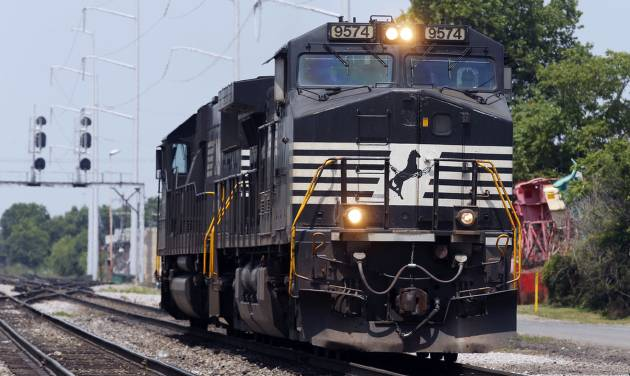 In this June 4, 2014 photo, a Norfolk Southern locomotive moves along the tracks in Norfolk, Va. Norfolk Southern Corp. on Wednesday, July 23, 2014 reported profit that climbed by 21 percent in its second quarter, and topped analysts' expectations. (AP Photo/Steve Helber)