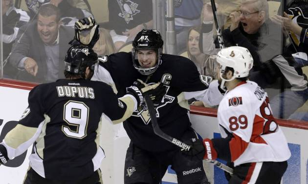 Pittsburgh Penguins' Sidney Crosby (87) celebrates scoring his second goal of the first period with teammate Pascal Dupuis (9) as Ottawa Senators' Cory Conacher (89) skates back to his bench during Game 2 of an NHL hockey Stanley Cup second-round playoff series, in Pittsburgh on Friday, May 17, 2013.(AP Photo/Gene J. Puskar)