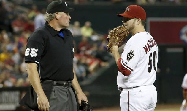 Umpire Ted Barrett (65) talks to Arizona Diamondbacks' Evan Marshall (50) for throwing behind Milwaukee Brewers' Ryan Braun during the seventh inning of a baseball game on Tuesday, June 17, 2014, in Phoenix.  On the next pitch Arizona Diamondbacks' Evan Marshall hit the Brewers' Braun. (AP Photo/Ross D. Franklin)