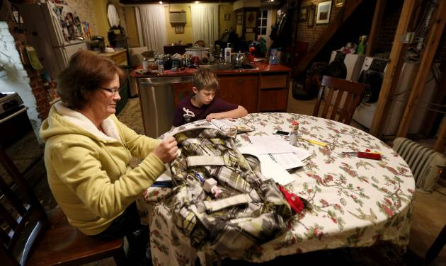 In this Thursday, Jan. 17, 2013 photo, Irene Sobolov, left, sits at a table while her 10-year-old son Joey Sobolov works on his fifth grade science homework in their home,  in Hoboken, N.J. The living and dining rooms of the Sobolov's home, which are below ground in the basement of their home, were damaged in the floods caused by Superstorm Sandy. Many people in Hoboken, Jersey City and Manhattan who live or have businesses in garden-level buildings have had their flood insurance claims denied, because full coverage does not extend to structures that are underground. Home and business owners are now eligible for grant money under the federal Sandy relief bill, but some are calling for the national flood insurance rules to be changed, saying they are unfair to urban areas. (AP Photo/Julio Cortez)