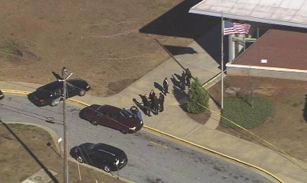 """In this image made from video and released by WSB-TV, authorities investigate the scene of a school shooting, Thursday, Jan 31, 2013 in Atlanta. Authorities say a 14-year-old has been wounded in a shooting at an Atlanta middle school and a suspect has been taken into custody. Atlanta police spokesman Carlos Campos says the wounded student has been taken """"alert, conscious and breathing"""" to Grady Hospital. (AP Photo/WSB-TV)"""