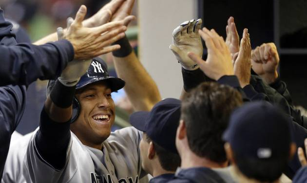 New York Yankees' Yangervis Solarte is congratulated in the dugout after his three-run home run against the Milwaukee Brewers in the fourth inning of a baseball game Friday, May 9, 2014, in Milwaukee. (AP Photo/Jeffrey Phelps)
