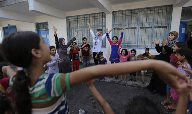 Volunteer Nisreen Shawa, 25, centre,  leads a play session with displaced Palestinian children at a U.N. school where they had sought refuge along with their families during the war, in Gaza City, Gaza Strip, Thursday, Aug. 7, 2014. Taking advantage of the continuing ceasefire, volunteers from the local non-profit NGO 'Tomooh' (Ambition), arranged a special play session for children to try and lessen the stress they've been enduring after the weeks of conflict. In the playground the children got a chance to sing and play group games under the caring eye of volunteers. They hope that their efforts will lessen the damage of the traumatic recent weeks events, or at least help them forget for a short while. (AP Photo/Lefteris Pitarakis)