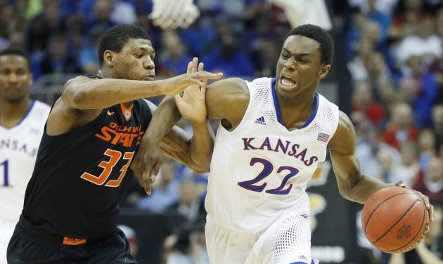 Kansas guard Andrew Wiggins (22) is covered by Oklahoma State guard Marcus Smart (33) during the second half of an NCAA college basketball game in the quarterfinals of the Big 12 Conference men's tournament in Kansas City, Mo., Thursday, March 13, 2014. Kansas defeated Oklahoma State 77-70 in overtime. (AP Photo/Orlin Wagner)