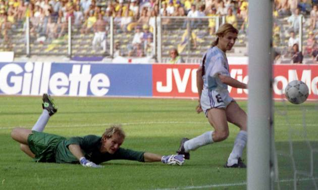 FILE - In this June 24, 1990 file photo, Argentina's Claudio Caniggia, right, scores, as the Brazilian goalkeeper Claudio Taffarel watches helplessly, during the World Cup second round soccer match, in Turin, Italy. On this day: Against the run of play, Argentina beats rival Brazil 1-0 to progress to the quarterfinals. (AP Photo/Luca Bruno, File)