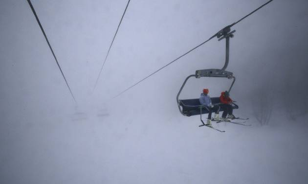 Skiers take a chair lift up the mountain in heavy fog near the alpine skiing training slopes at the Sochi 2014 Winter Olympics, Monday, Feb. 17, 2014, in Krasnaya Polyana, Russia. (AP Photo/Christophe Ena)