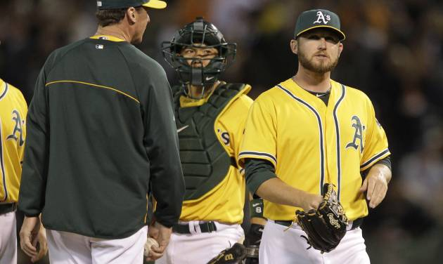 Oakland Athletics relief pitcher Ryan Cook, right, walks to the dugout after being taken out of the game by manager Bob Melvin, left, as catcher Kurt Suzuki, center, looks on in the ninth inning of their interleague baseball game against the San Francisco Giants in Oakland, Calif., Friday, June 22, 2012. (AP Photo/Eric Risberg)