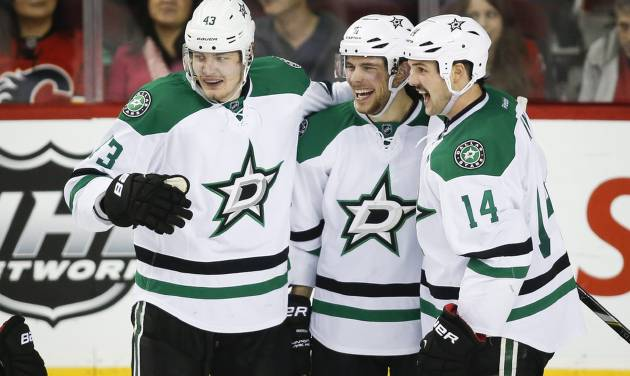 Dallas Stars' Tyler Seguin, centre, celebrates his goal with teamates Valeri Nichushkin, left, from Russia, and Jamie Benn during third period NHL hockey action against the Calgary Flames in Calgary, Alta., Thursday, Nov. 14, 2013. The Dallas Stars beat the Calgary Flames 7-3. (AP Photo/The Canadian Press, Jeff McIntosh)