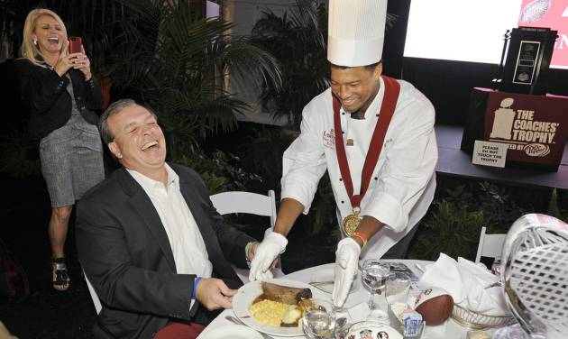 Florida State NCAA college football coach Jimbo Fisher laughs as he is served dinner by Florida State quarterback and Heisman Trophy winner Jameis Winston, Thursday night, Jan. 2, 2014 at Lawry's Beef Bowl in  Beverly Hills, Calif. At left is coach Fisher's wife, Candi. Florida State and Auburn will play in the BCS Championship game on Monday, Jan. 6 in Pasadena.  (AP Photo/The Florida Times-Union/Bob Self)