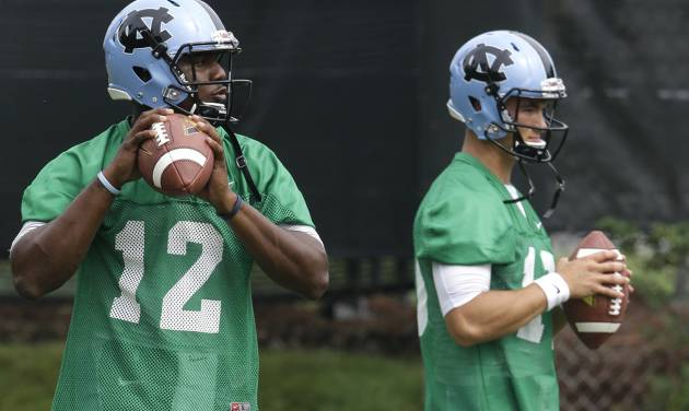 In this photo taken Friday, Aug. 1, 2014,  North Carolina quarterbacks Marquise Williams (12) and Mitch Trubisky, right, participate in a passing drill during an NCAA  football practice in Chapel Hill, N.C. (AP Photo/Gerry Broome)