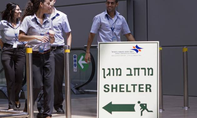 Israelis airport workers pass a sign pointing to a shelter for refuge in case a warning siren indicates the possibility of an incoming rocket, at Ben Gurion International airport a day after the U.S. Federal Aviation Administration imposed a 24-hour restriction on flights after a Hamas rocket landed within a mile of the airport, in Tel Aviv, Israel, Wednesday, July 23, 2014. U.S. Secretary of State John Kerry flew into Israel's main airport Wednesday despite a Federal Aviation Administration ban in an apparent sign of his determination to achieve a cease-fire agreement in the warring Gaza Strip despite little evidence of progress in ongoing negotiations. (AP Photo/Dan Balilty)