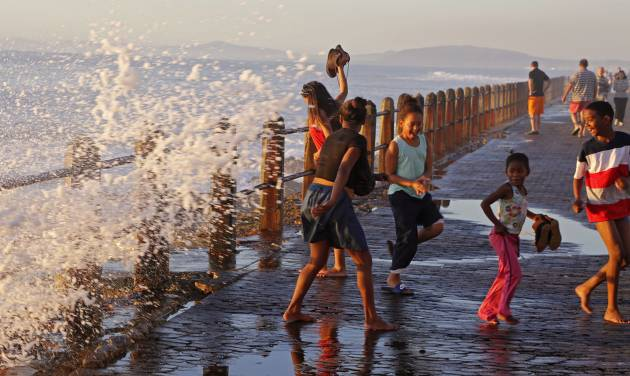 In this photo taken on Sunday, Aug. 24, 2014, children, right, react as they are sprayed by a wave on the promenade, a popular tourist hotspot near the city of Cape Town, South Africa. This is the perfect vantage point to see arrogant sea gulls, waves crashing onto rocks and miles of Atlantic beaches. With the taste of sea salt in the air, you can walk, jog or sit on a bench to view the Mother City. (AP Photo/Schalk van Zuydam)