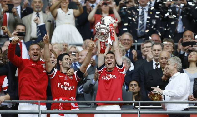 Arsenal's club captain Thomas Vermaelen holds the trophy aloft as he celebrates after his team won the English FA Cup final soccer match between Arsenal and Hull City at Wembley Stadium in London, Saturday, May 17, 2014. Arsenal won 3-2 after extra-time. (AP Photo/Kirsty Wigglesworth)