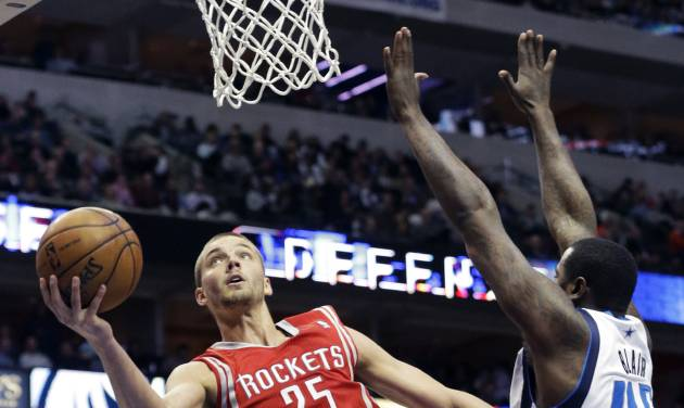 Houston Rockets forward Chandler Parsons (25) drives to the basket between Dallas Mavericks center DeJuan Blair (45) and Devin Harris during the second half of an NBA basketball game Wednesday, Jan. 29, 2014, in Dallas. Parsons scored a team high 26 points in the Rockets 117-115 win. (AP Photo/LM Otero)
