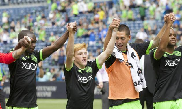 Along with Seattle Sounders teammates Jalil Anibaba, far left, Clint Dempsey, second from right, and Tristan Bowen far right, Xander Bailey acknowledges fans following a friendly soccer match against Tottenham Hotspur in Seattle, Saturday, July 19, 2014. The match ended in a 3-3 draw. (AP Photo/Stephen Brashear)