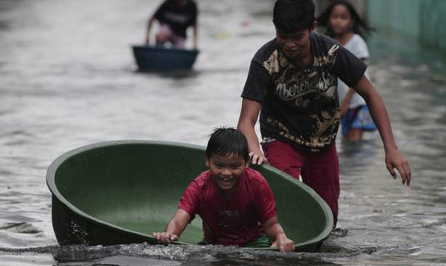 A Filipino boy plays along a flooded street in Obando town, Bulacan province, north of Manila, Philippines Tuesday July 31, 2012. Typhoon Saola dumped torrents of rain as it swept past the Philippines, killing at least seven people and displacing more than 20,000 others by Tuesday. (AP Photo/Aaron Favila)