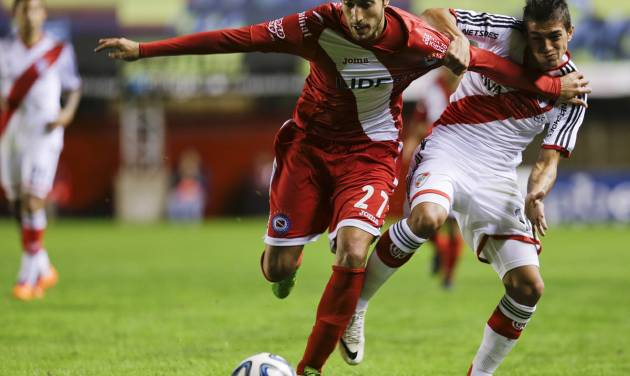 Argentinos Juniors's Franco Flores, left, fights for the ball with River Plate's Manuel Lanzini during an Argentine league soccer match in Buenos Aires, Argentina, Sunday, May 11, 2014. (AP Photo/Natacha Pisarenko)