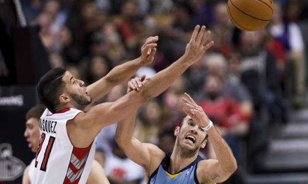 Toronto Raptors guard Greivis Vasquez, left, battles for the loose ball against Memphis Grizzlies guard Nick Calathes, right, during first half NBA basketball action in Toronto on Friday, March. 14, 2014. (AP Photo/The Canadian Press, Nathan Denette)