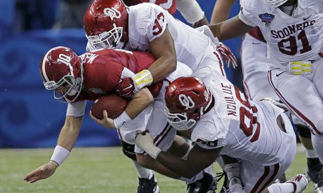 Alabama quarterback AJ McCarron (10) is sacked by Oklahoma defensive tackles Jordan Wade (93) and  Chuka Ndulue (98) during the second half of the NCAA college football Sugar Bowl in New Orleans, Thursday, Jan. 2, 2014. (AP Photo/Patrick Semansky)