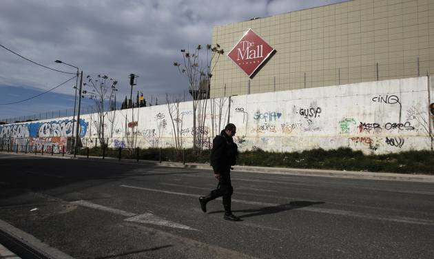A police officer secures the street in front of a mall following a blast in Athens, Sunday, Jan. 20 2013. A bomb exploded Sunday at a shopping mall in Athens, slightly wounding two security guards, police said. (AP Photo/Kostas Tsironis)