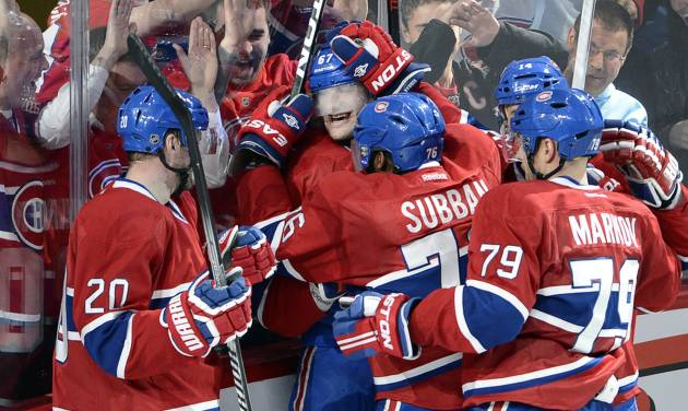 Montreal Canadiens left wing Max Pacioretty (67) is mobbed by teammates after scoring the winning goal against the Tampa Bay Lightning during third period National Hockey League Stanley Cup playoff action on Tuesday, April 22, 2014 in Montreal. (AP Photo/The Canadian Press, Ryan Remiorz)