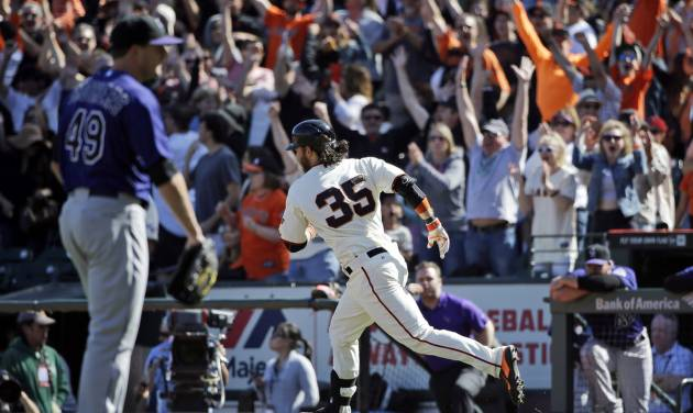 San Francisco Giants' Brandon Crawford runs down the first base line during his walk-off home run off Colorado Rockies relief pitcher Rex Brothers, left, during the 10th inning of a baseball game on Sunday, April 13, 2014, in San Francisco. San Francisco won 5-4. (AP Photo/Marcio Jose Sanchez)