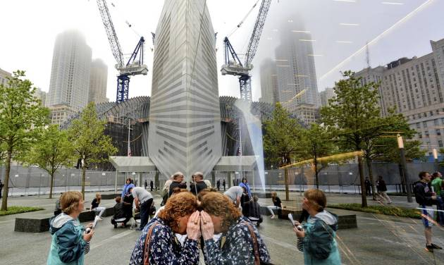 People try to look through the windows of the National September 11 Memorial Museum during the museum's dedication in New York, on Thursday, May 15, 2014. (AP Photo/Justin Lane, Pool)