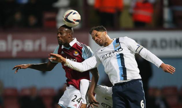 West Ham's Carlton Cole, left goes to head the ball with Manchester City's Joleon Lescott during the second leg of the English League Cup semifinal soccer match between West Ham United and Manchester City in London, Tuesday, Jan. 21, 2014. (AP Photo/Alastair Grant)