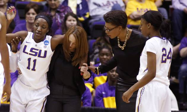 In a March 23, 2014 photograph, LSU guard Raigyne Moncrief (11) is helped off the floor by a trainer after injuring her left knee, as basketball coach Nikki Caldwell, right, and teammate DaShawn Harden (24) check on her in the second half of an NCAA college basketball first-round tournament game against Georgia Tech in Baton Rouge, La. LSU officials said Moncrief was to be examined by doctors Monday and her playing status would be determined prior to the start of the second round game Tuesday night. (AP Photo/Rogelio V. Solis)