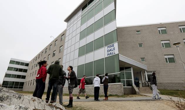UMASS-Dartmouth students stand outside he Pine Dale Hall dormitory that Dzhokhar Tsamaev, lived in on Friday, April 19, 2013 in Dartmouth, Mass., as students were evacuated from campus on Friday, April 19, 2013, as local and state officials investigate the dorm room of Tsarnaev, 19,  one of the two suspects wanted for the Boston Marathon bombing on Monday. The campus closed down along with colleges around the Boston area.  (AP Photo/Standard Times, Peter Pereira)  MANDATORY CREDIT