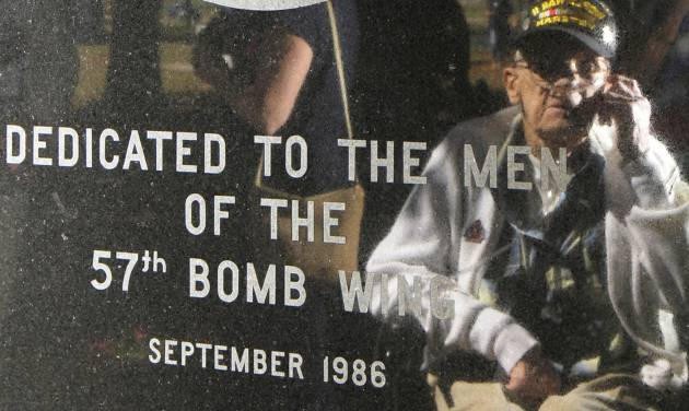 In this Sept. 27, 2013 photo Lenard Wichtowski is reflected in the memorial to the 57th Bomb Wing during a reunion outside the U.S. Air Force Museum at Wright Patterson Air Force base in Dayton, Ohio. According to the Department of Veteran Affairs, just a little over 1 million World War II veterans remain. They are in their 80s and 90s, and many are infirm or fragile. The sparsely attended reunions are yearly reminders of the passing of the Greatest Generation. (AP Photo/Tom Uhlman)