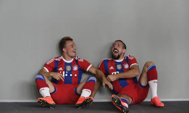Bayern Munich's Xherdan Shaqiri, left, and Franck Ribery joke during an official photo shoot for the new German first division Bundesliga season in Munich, southern Germany, Saturday, Aug. 9, 2014. (AP Photo/Matthias Schrader)