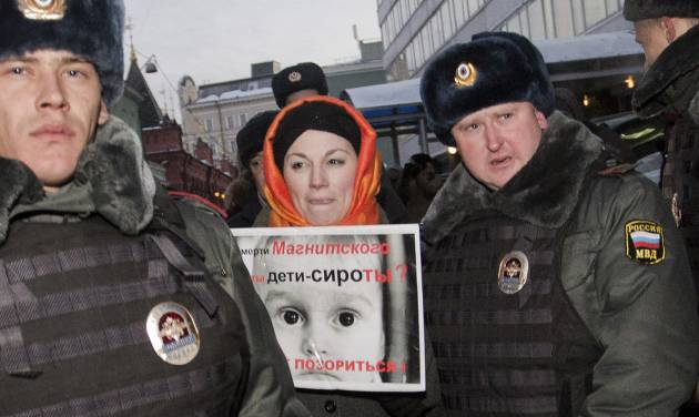 Police officers detain a protester near the State Duma, in Moscow, Russia, Wednesday, Dec. 19, 2012. People picket parliament's lower chamber, to protest against planned debate of an amendment that would ban Americans from adopting Russian children. The poster reads: Are orphans guilty of Magnitsky's death ? Stop putting shame on yourselves! Sergei Magnitsky, a Russian lawyer who was arrested by the officials he accused of a $230 million tax fraud. He was repeatedly denied medical treatment and in 2009 died in jail. (AP Photo/Novaya Gazeta, Yevgeny Feldman)