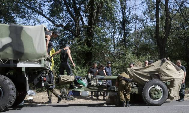 Ukrainian soldiers park their hardware on roadside as they are waiting for the start of the march into the town of Mariupol, eastern Ukraine, Wednesday, Aug. 27, 2014. Heavy shelling hit a town of Novoazovsk in southeastern Ukraine on Wednesday, the third day of an assault that has forced government troops to spread their ranks thinner along the Russian border. Ukraine claimed the shelling was coming both from pro-Russian separatists and from Russia itself. (AP Photo/Sergei Grits)