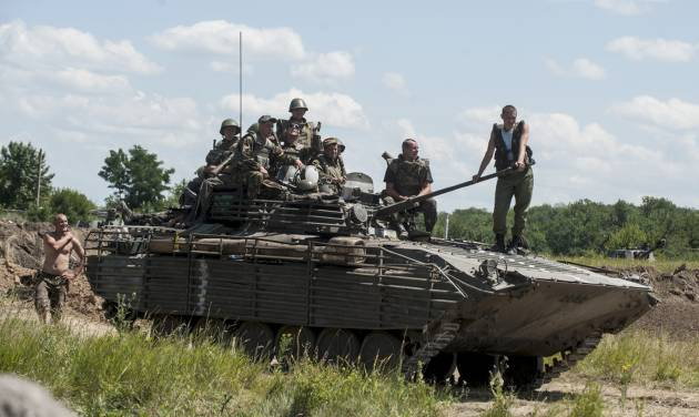 Ukrainian troops atop an APC at a checkpoint near Slovyansk, eastern Ukraine, Saturday, July 5, 2014. Ukraine's forces claimed a significant success against pro-Russian insurgents on Saturday, chasing them from one of their strongholds in the embattled east of the country. Rebels fleeing from the city of Slovyansk vowed to regroup elsewhere and fight on. (AP Photo/Evgeniy Maloletka)
