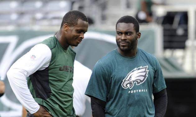 FILE - In this Aug. 29, 2013, file photo, New York Jets quarterback Geno Smith, left, talks to Philadelphia Eagles quarterback Michael Vick before a preseason NFL football game in East Rutherford, N.J. The Jets signed the former Philadelphia Eagles quarterback to a one-year deal Friday, March 21, 2014, and released Mark Sanchez, the one-time face of the franchise.   (AP Photo/Bill Kostroun, File)