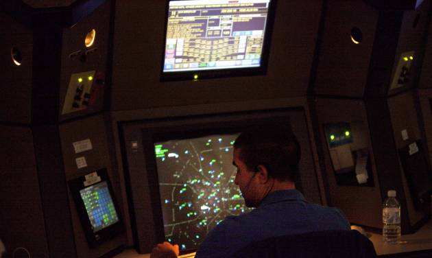 FILE -This April 18, 2011 file photo shows an air traffic controller working in a terminal radar approach control room at the Atlanta TRACON in Peachtree City, Ga. Air traffic controller furloughs scheduled to kick in on Sunday could result in flight delays of more than three hours in Atlanta, as well as significant delays in Chicago, Los Angeles and New York-area airports, federal officials said Thursday. (AP Photo/David Goldman, File-Pool)