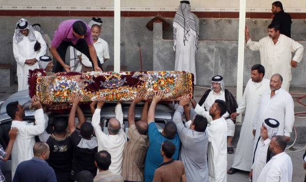 Mourners unload the coffin of Imad Younis, 22, who was killed in a car bomb attack, in the Shiite holy city of Najaf, 100 miles (160 kilometers) south of Baghdad, Iraq, Thursday, Aug. 15, 2013. A wave of car bombs  on Wednesday killed and wounded dozens of people, the latest attacks in a months-long surge in violence. More than 3,000 people have been killed in violence during the past few months, raising fears Iraq could see a new round of widespread sectarian bloodshed similar to that which brought the country to the edge of civil war in 2006 and 2007. (AP Photo/Haider Hamdani)
