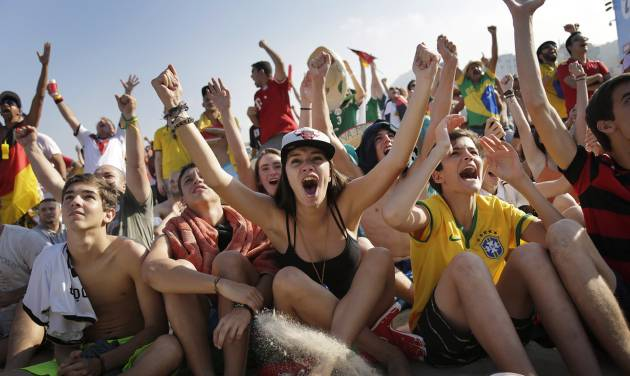 Soccer fans, many supporting Germany, raise their arms and cheer at the FIFA Fan Fest area on Copacabana beach, after Thomas Mueller scored Germany's fourth goal against Portugal on Monday, June 16, 2014  in Rio de Janeiro, Brazil, during Germany's World Cup soccer match with Portugal.(AP Photo/Wong Maye-E)
