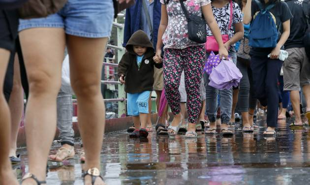 """Pedestrians walk during a slight rain brought about by typhoon Melor (local name """"Nona"""") at suburban Taguig city, southeast of Manila, Philippines, Wednesday, Dec. 16, 2015. Typhoon Melor left wide areas without power as it crossed over the central Philippines with classes, flights and ferry trips remaining suspended in affected areas Wednesday. About 730,000 people were evacuated to safer grounds before the storm hit. The government weather bureau said the typhoon had weakened but was still packing winds of 140 kilometers (87 miles) per hour and gusts of up to 170 kph (106 mph) as it passed over Oriental Mindoro province. (AP Photo/Bullit Marquez)"""